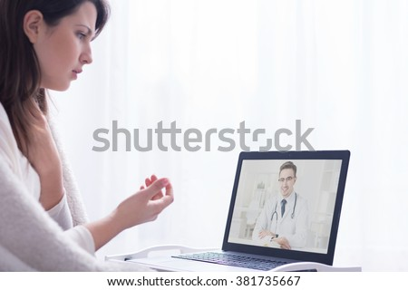 Ill woman during web consultation with doctor, sitting in front of computer