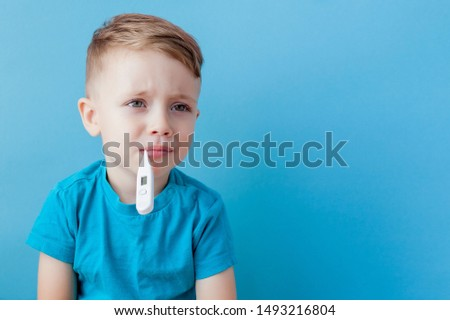 Ill young child with a thermomether, measuring the height of his fever and looking into the camera.
