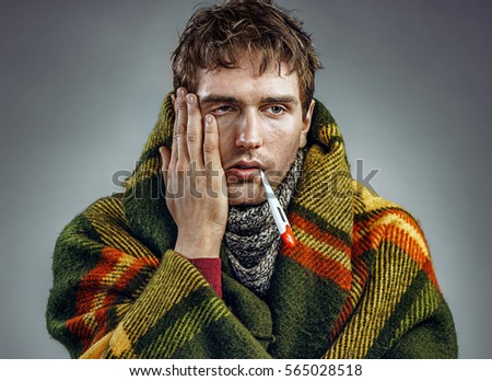 Ill young man with a thermometer in his mouth wrapped in plaid. Healthcare concept
