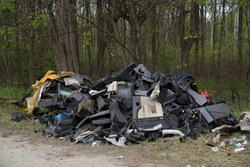 Illegal garbage hill by the road, plastic and other waste. Dangerous pollution in nature. Terrible garbage in the woods. Europe Hungary - 05.02.2020.