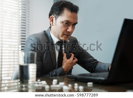 Illness, stressed, tired, exhausted, pain from overworked concepts. Asian Businessman has heart attack. Pills with water on foreground.