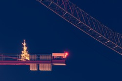 Illuminated and decorated christmas tree standing on arm of very tall tower crane at night