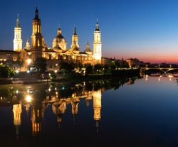 Illuminated Basilica of Our Lady of the Pillar on the banks of the Ebro river at sunset in Zaragoza, Spain