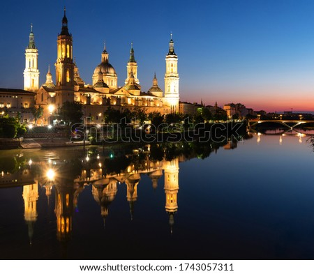 Illuminated Basilica of Our Lady of the Pillar on the banks of the Ebro river at sunset in Zaragoza, Spain Foto stock ©