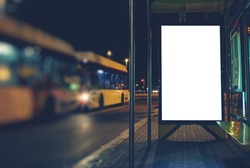 Illuminated blank billboard with copy space for your text message or content, advertising mock up banner of bus station, public information board in night city, auto bus stop empty poster