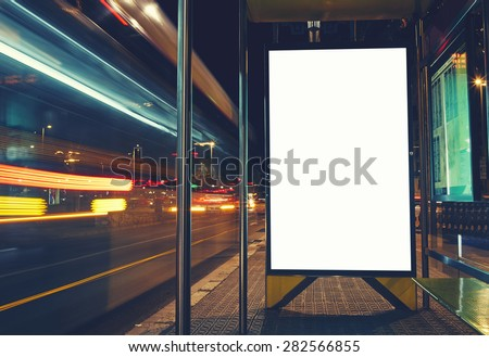 Illuminated blank billboard with copy space for your text message or content, advertising mock up banner of bus station, public information board with blurred vehicles in high speed in night city