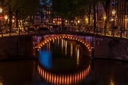 Illuminated bridge at twilight along a canal in Amsterdam