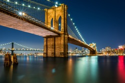 Illuminated Brooklyn Bridge by night as viewed from the Manhattan side - very long exposure for a perfectly smooth water