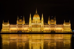 Illuminated Budapest parliament building at night with dark sky and reflection in Danube river