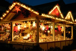 Illuminated Christmas fair kiosk with loads of shining decoration merchandise, no logos