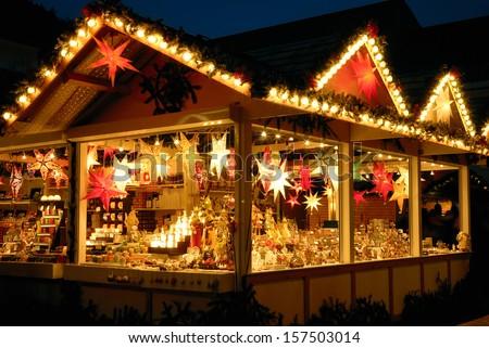 Illuminated Christmas fair kiosk with loads of shining decoration merchandise no logos