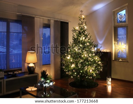 Illuminated Christmas tree decorated in modern living room