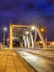 Illuminated draw bridge in Port of Antwerp harbor area at twilight, Belgium.