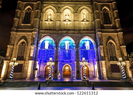 Illuminated Front of the Notre-Dame Basilica in Montreal, with Christmas decorations, at night. (With a little digital noise in the sky)