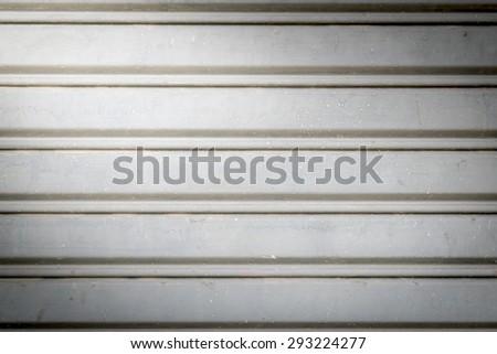 illuminated grunge-metallic roller auto shutter door with light from corner