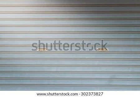illuminated grunge metallic roller auto shutter door with light from corner