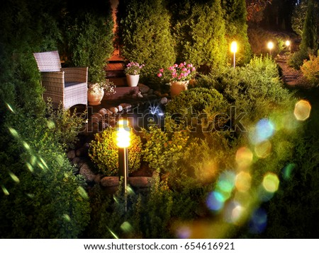 Illuminated home garden patio plants and evening party lights near small fountain #654616921