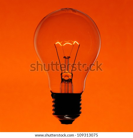 Illuminated incandescent lamp bulb isolated on orange gradient background