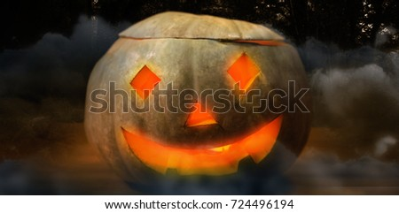 Illuminated jack o lantern on wooden table against way between trees