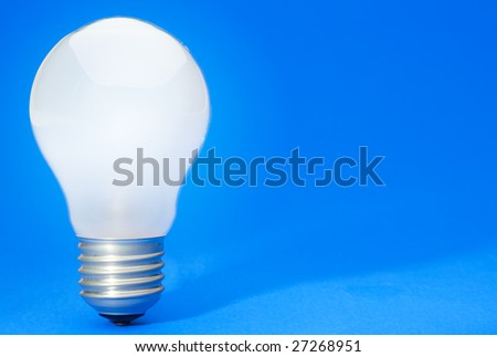 Illuminated light bulb on blue studio lit background