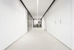 Illuminated long corridor in modern office building