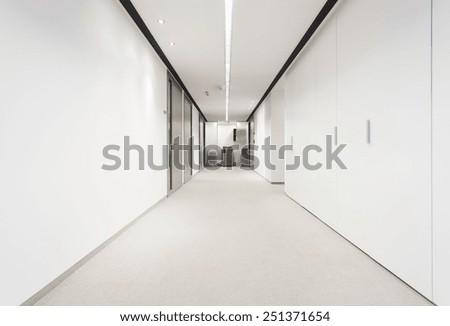 Illuminated long corridor in modern office building Foto stock ©