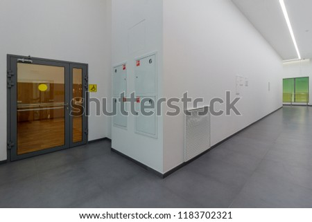Illuminated long corridor in modern office building with glass doors #1183702321