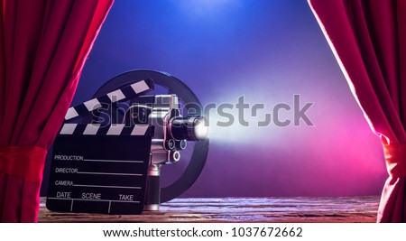 Photo of  Illuminated Movie Camera With Clapperboard And Film Reel Against Colored Background