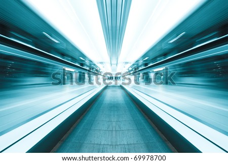 illuminated moving blue escalator inside contemporary airport