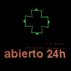 Illuminated night pharmacy sign on. With the message open 24 hours a day in Spanish