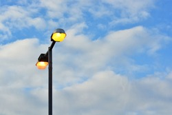 Illuminated outdoor streetlights at day time on the background of the blue sky.