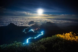 Illuminated path to the top of the mountain of Adam?? Peak with moon and stars in the sky. View from Adam?? Peak, Sri Lanka