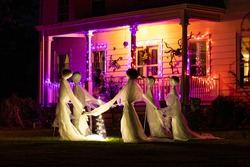 Illuminated scary Halloween house ghosts decoration at night