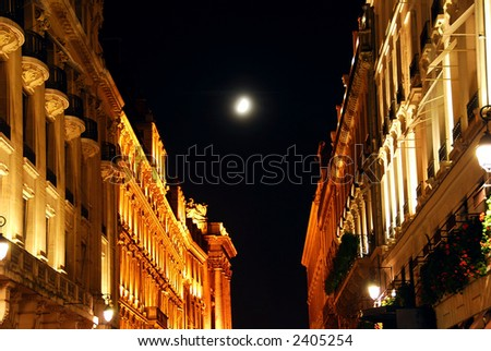 Illuminated street in Paris France at night with bright moon