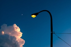 Illuminated street light and pole against blue evening sky with cloud and moon.