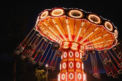 Illuminated swing chain carousel in amusement park at night
