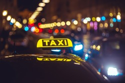 Illuminated taxi sign on top of a car. City lights with neon color in the background. Rainy urban night scene.