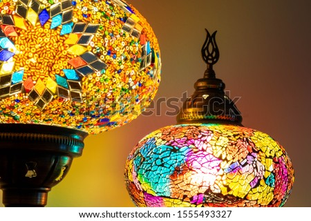 Illuminated Turkish Moroccan handmade stain glass lamps. Vibrant and colourful giving home décor a cosy feel. Copy space, blurred background, home style concept. Awesome traditional background.