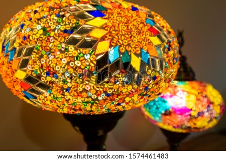 Illuminated Turkish Moroccan handmade stain glass lamps. Vibrant and colourful giving home décor a cosy feel. Copy space, blurred background, home style concept. Awesome traditional background. #1574461483