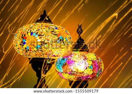 Illuminated Turkish Moroccan handmade stain glass lamps. Vibrant and colourful with unique light flare flashes, trails, streaks running through. Antique bronze. Traditional Background concept. Blurred