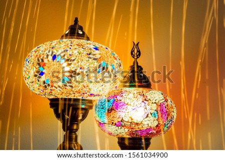 Illuminated Turkish Moroccan handmade stain glass lamps. Vibrant and colourful with unique light flare flashes, trails, streaks running through. Antique bronze. Traditional Background concept.