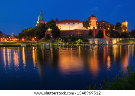 Illuminated Wawel Royal Castle in the evening. Beautiful reflection in the Wisla river. Krakow, Lesser Poland, Poland. #1548969512
