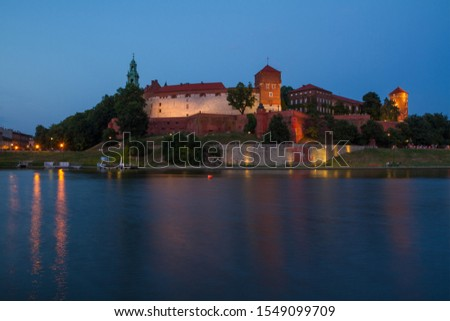 Illuminated Wawel Royal Castle in the evening. Beautiful reflection in the Wisla river. Krakow, Lesser Poland, Poland. #1549099709
