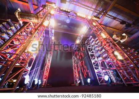 Illuminated way to boxing ring inside fight club; multi-colored lights