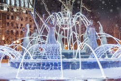 Illuminated with garlands and twinkling lights fountain in the center of Ufa, Russia. Christmas and New Year decorations and holidays.