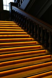 Illuminated wooden stairs with yellow LED lights in the dark