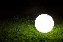 illuminating a spherical ground garden lamp of white color lies on a green lawn in the grass in the backyard of the park, closeup of a lighting fixture a night scene in the dark.
