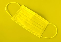 Illuminating yellow panton color 2021 medical mask. Selective, soft focus. Horizontal orientation, top view.