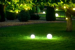 illumination garden light with electric ground lantern with ball diffuser lamp on meadow with garland of warm light bulbs on tree branch with leaves with landscaping, illuminate evening scene nobody.