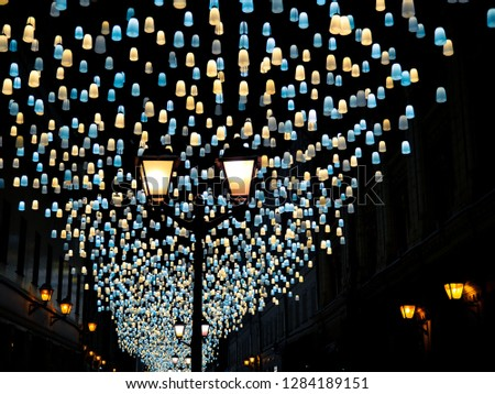 Illumination on Stoleshnikov lane in Moscow, Russia. Hanging lamps over street with old fashioned buildings and vintage streetlights. Garlands rows stretched across the street. Perspective view.  #1284189151